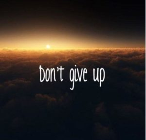 A sunset over clouds with the words dont give up