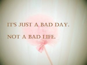 "A sign with a flower in the background that says ""It's just a bad day, not  bad life"""