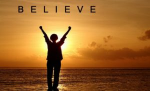 A person holding their hands in the air in triumph on a beach with the sea and a sunset in the background with the word believe at the top.