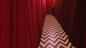 Agent Dale Cooper (played by actor Kyle Mcklachlan) at the end of a long corridor of red curtains with a black and white zig zagged floor in the black lodge in twin peaks