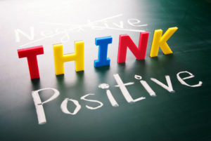 A sign saying negative think positive but the negative is crossed out.
