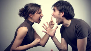 A man and a woman shouting at each other and raising hands and clenching fists showing a bad relationships